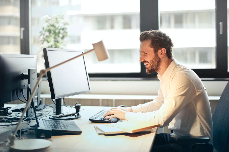 Ein Mann hat Freude mit Prokommunal am Computer